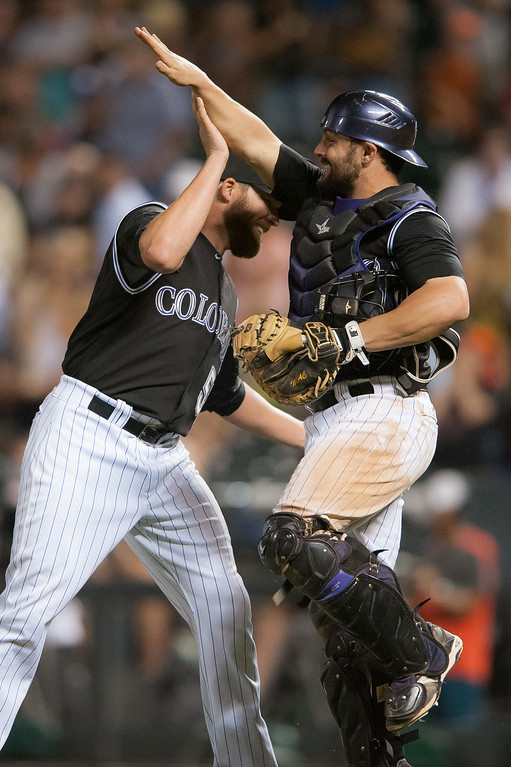. DENVER, CO - AUGUST 06:  Michael McKenry #8 and Brooks Brown #51 of the Colorado Rockies celebrate the 13-4 win over the Chicago Cubs after a game at Coors Field on August 6, 2014 in Denver, Colorado.  (Photo by Dustin Bradford/Getty Images)