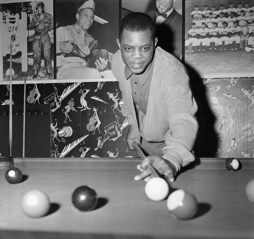 . Willie Mays, San Francisco Giants center fielder, lines up shot on pool table in recreation room of his New York home on Jan. 21, 1959. Willie is reported to have agreed (the day before) to an $80,000 contract for the coming year. (AP Photo/John Rooney)