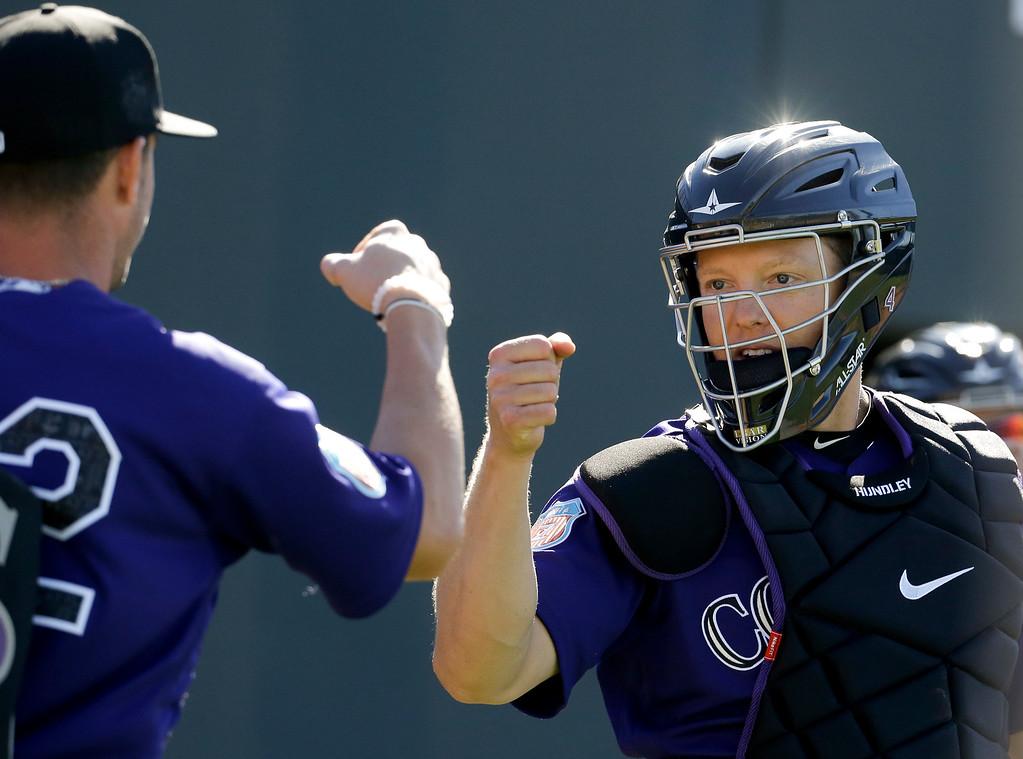 . Colorado Rockies catcher Nick Hundley, right, greets starting pitcher Chris Rusin during spring training baseball practice in Scottsdale, Ariz., Monday, Feb. 22, 2016. (AP Photo/Chris Carlson)
