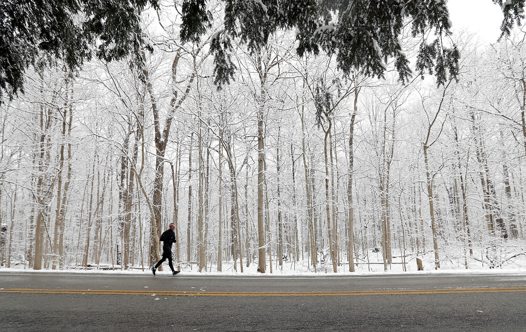 . A runner goes for a run in Eagle Creek Park as snow falls Tuesday, Dec. 13, 2016, in Indianapolis. (AP Photo/Darron Cummings)