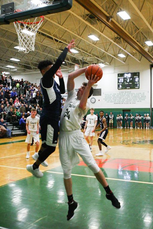 . 2018 - Basketball - Benedictine at Lake Catholic.  Benedictine defeated Lake Catholic 63-56.  Lake Catholic\'s Jack LeJuene (24) tries to get a shot off past Benedictine\'s Eric Buckner (3).