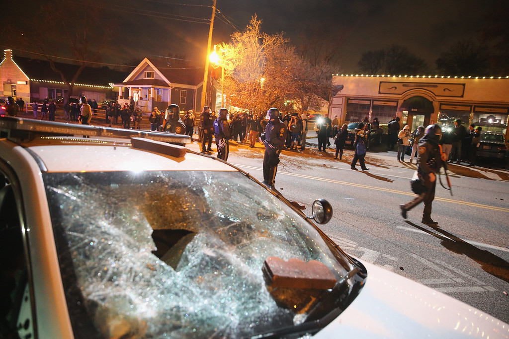 . A damaged squad car sits nearby as police confront protestors after riioting broke out following the grand jury announcement in the Michael Brown case on November 24, 2014 in Ferguson, Missouri. Ferguson has been struggling to return to normal after Brown, an 18-year-old black man, was killed by Darren Wilson, a white Ferguson police officer, on August 9. His death has sparked months of sometimes violent protests in Ferguson. A grand jury today declined to indict officer Wilson.  (Photo by Scott Olson/Getty Images)