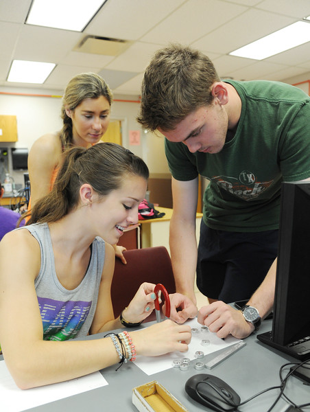 Students Kalli Hanson(left), Lauren McGregor and Paul Voyles(right) determine the magnetic field lines of the horseshoe magnet in Physics lab.