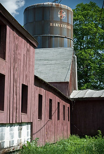 The side of the hay barn with a silo in the background.