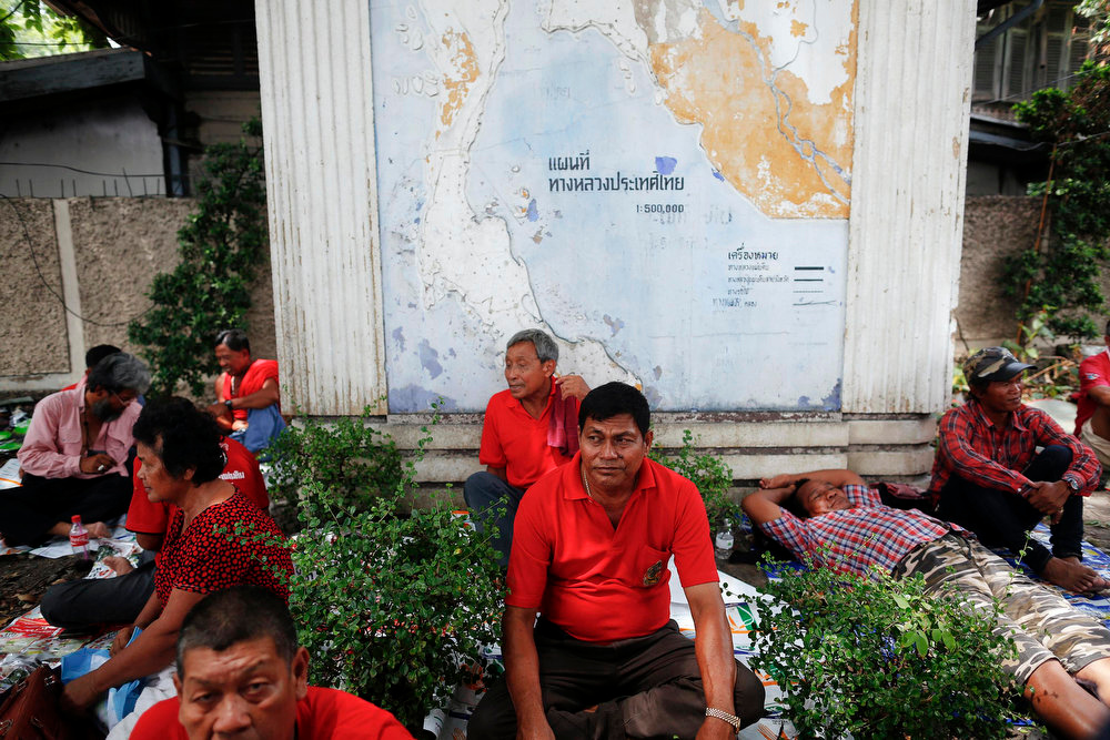 """. Members of the \""""red shirt\"""" movement rest in front of a map of Thailand during a gathering near the Democracy Monument, the site of bloody clashes with Thai security forces, in Bangkok on April 10, 2013. Supporters of Thaksin Shinawatra, the former prime minister, and members of the \""""red shirt\"""" movement gathered in Bangkok on Wednesday to mark the third anniversary of bloody clashes and to commemorate their deceased comrades.   REUTERS/Damir Sagolj"""