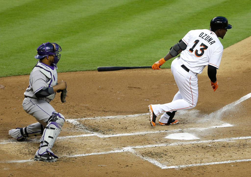 . Miami Marlins\' Marcell Ozuna (13) hits a single as Colorado Rockies catcher Wilin Rosario, left, looks on in the second inning of a baseball game, Tuesday, April 1, 2014, in Miami. (AP Photo/Lynne Sladky)