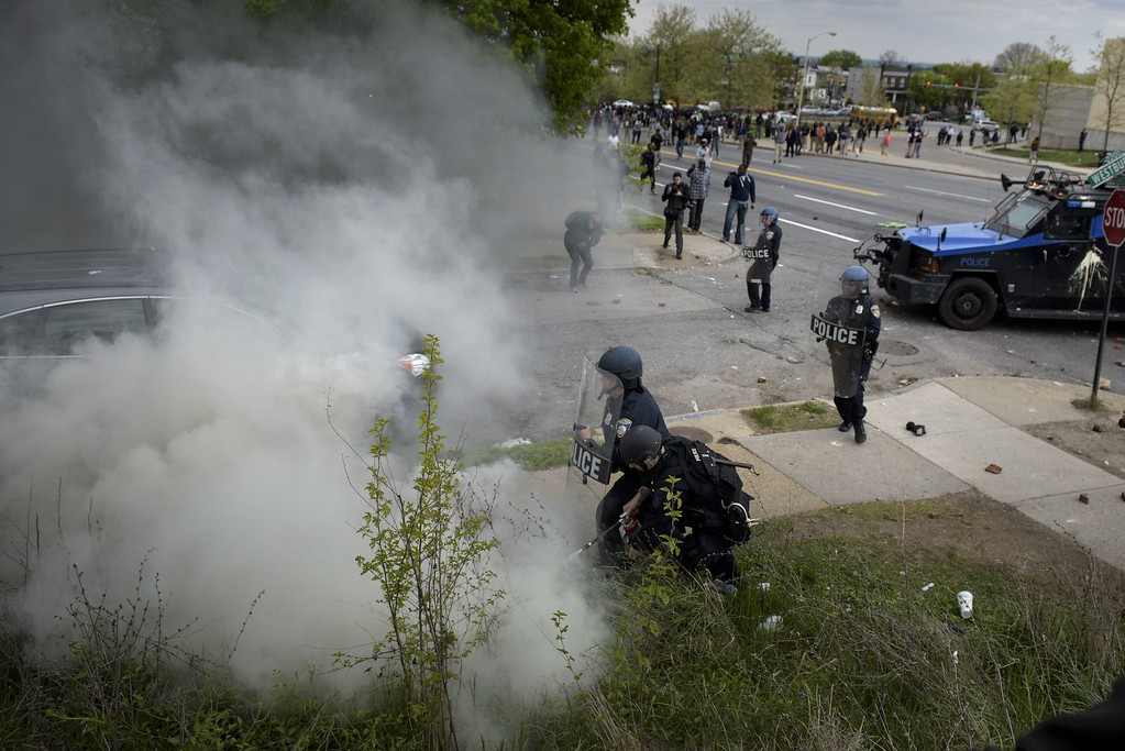 . Police put out a fire caused by a teargas canister April 27, 2015 in Baltimore, Maryland. Violent street clashes erupted in Baltimore on Monday after friends and family gathered for the funeral of Freddie Gray, a 25-year-old black man whose death in custody triggered a fresh wave of protests over US police tactics. Police said at least seven officers were injured -- one of them was unresponsive -- as youths hurled bricks and bottles and destroyed at least one police vehicle in the vicinity of a shopping mall not far from the church where the funeral took place.  BRENDAN SMIALOWSKI/AFP/Getty Images