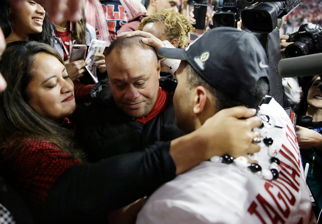 . Alabama\'s Tua Tagovailoa celebrates with his parents Galu and Diane after overtime of the NCAA college football playoff championship game against Georgia Monday, Jan. 8, 2018, in Atlanta. Alabama won 26-23. (AP Photo/David Goldman)