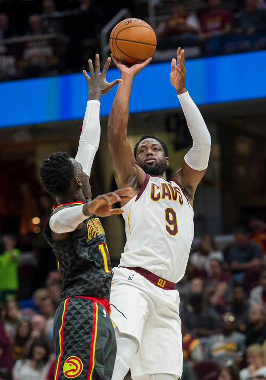 . Cleveland Cavaliers\' Dwayne Wade (9) shoots over Atlanta Hawks\' Dennis Schroder during the first half of an NBA pre-season basketball game in Cleveland, Wednesday, Oct. 4, 2017. (AP Photo/Phil Long)