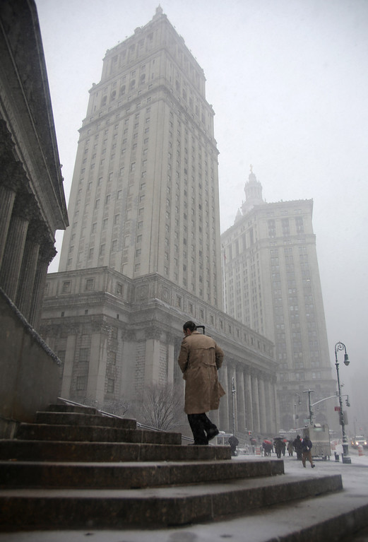 . A man climbs courthouse steps in lower Manhattan during a storm on Friday, March. 8 2013, in New York. A very wet snow is causing slippery road conditions in the metropolitan area and several inches have fallen on eastern Long Island and Westchester, Rockland and Putnam counties.(AP Photo/Peter Morgan)