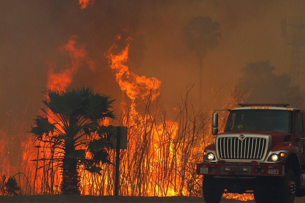 . A fire engine drives past flames from the Springs Fire at Point Mugu State Park May 3, 2013.  REUTERS/Jonathan Alcorn