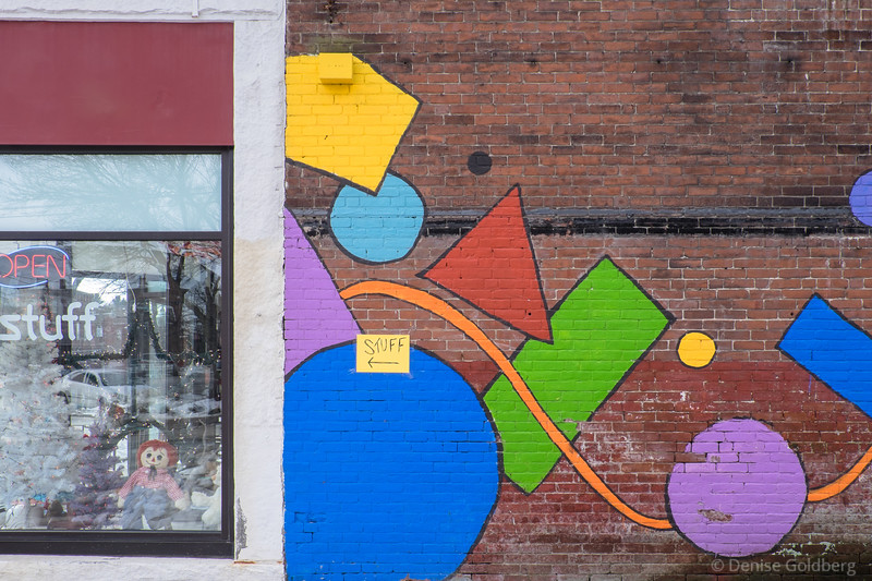 """a store selling """"STUFF"""", a sign attached to a mural in Turners Falls, MA"""