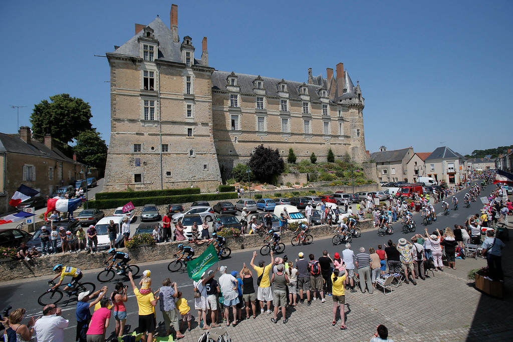 . The pack with Christopher Froome of Britain, wearing the overall leader\'s yellow jersey, passes, bottom left corner, passes Durtal castle during the twelfth stage of the Tour de France cycling race over 218 kilometers (136.2 miles) with start in in Fougeres and finish in Tours, western France, Thursday July 11 2013. (AP Photo/Christophe Ena)