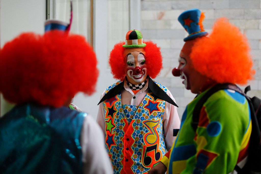 . In this Monday, Oct. 21, 2013 photo, clowns chat after registering to attend the 17th International Clown Convention in Mexico City.  The goal of the convention is to professionalize clowns in Latin America and highlight the need for a School of Clown Arts in Mexico. (AP Photo/Dario Lopez-Mills)