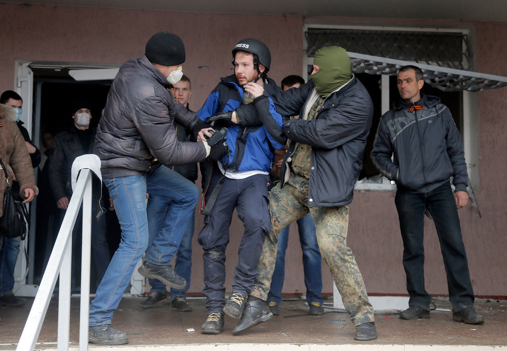 . Masked pro-Russian men attack British photojournalist Frederick Paxton during the mass storming of a police station in the eastern Ukrainian town of Horlivka Monday, April 14, 2014.   (AP Photo/Efrem Lukatsky)