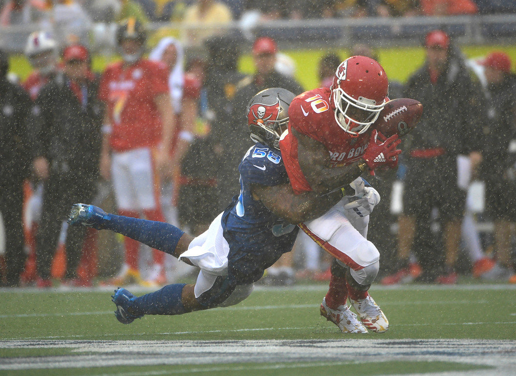 . AFC receiver Tyreek Hill (10), of the Kansas City Chiefs, drops the ball as NFC linebacker Kwon Alexander (58), of the Tampa Bay Buccaneers makes the tackle, during the first half of the NFL Pro Bowl football game, Sunday, Jan. 28, 2018, in Orlando, Fla. (AP Photo/Phelan M Ebenhack)
