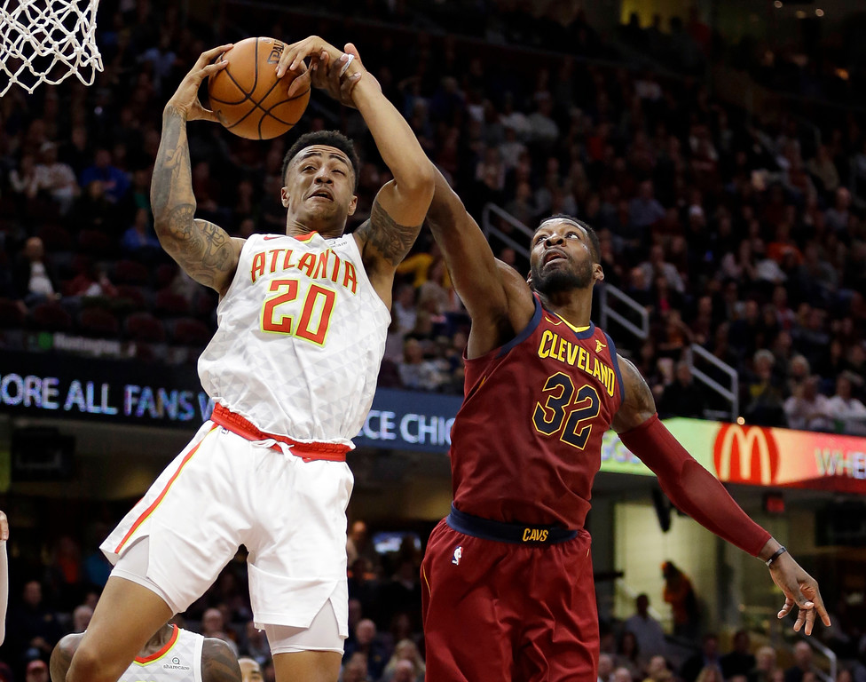 . Atlanta Hawks\' John Collins (20) grabs a rebound ahead of Cleveland Cavaliers\' Jeff Green (32) in the second half of an NBA basketball game, Sunday, Nov. 5, 2017, in Cleveland. (AP Photo/Tony Dejak)