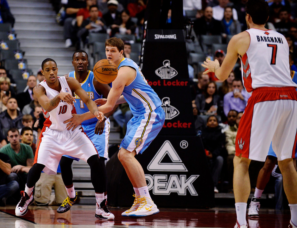 . Toronto Raptors\' DeMar DeRozan (L) passes the ball past Denver Nuggets\' Timofey Mozgov to teammate Andrea Bargnani (R) during the first half of their NBA basketball game in Toronto February 12, 2013.  REUTERS/Jon Blacker