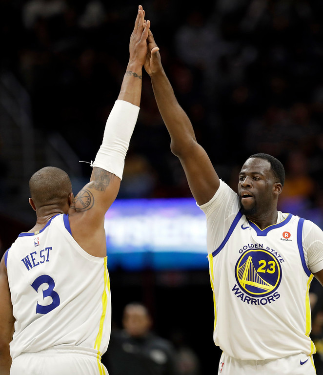 . Golden State Warriors\' Draymond Green (23) and David West (3) celebrate in the second half of an NBA basketball game against the Cleveland Cavaliers, Monday, Jan. 15, 2018, in Cleveland. (AP Photo/Tony Dejak)