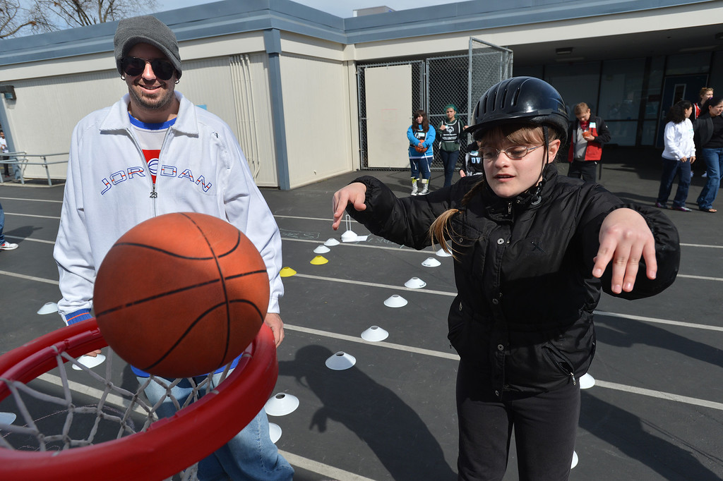 . John Place, an instructional assistant for the Contra Costa County Office of Education\'s East County Student Programs, looks on as Hope, 10,  of Deer Valley High School in Antioch, shoots a basketball during a Special Olympics basketball skills event at Turner Elementary School in Antioch, Calif., on Friday March 8, 2013.  (Dan Rosenstrauch/Staff)
