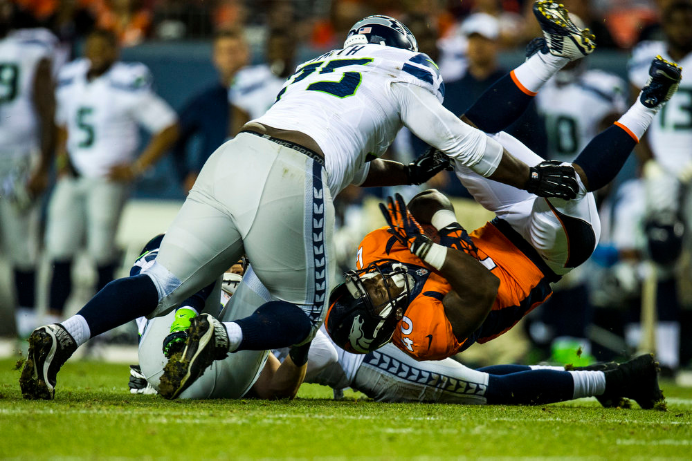 . Juwan Thompson (40) running back of the Denver Broncos is upended by D\'Anthony Smith (75) defensive tackle of the Seattle Seahawks during a preseason game between the Denver Broncos and the Seattle Seahawks at Sports Authority Field at Mile High on Thursday, August 07, 2014 in Denver, Colorado.  (Photo by Kent Nishimura/The Denver Post)