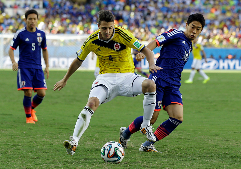 . Japan\'s Shinji Kagawa, right, challenges Colombia\'s Santiago Arias during the group C World Cup soccer match between Japan and Colombia at the Arena Pantanal in Cuiaba, Brazil, Tuesday, June 24, 2014. (AP Photo/Kirsty Wigglesworth)