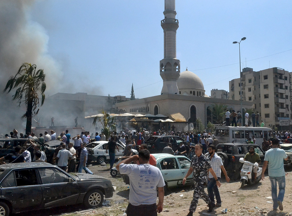 . Lebanese citizens gather outside a mosque which was attacked by a car bomb, in the northern city of Tripoli, Lebanon, Friday, Aug. 23, 2013.  (AP Photo)
