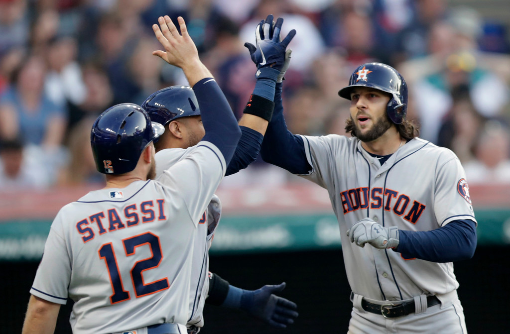 . Houston Astros\' Jake Marisnick, right, is congratulated by Yuli Gurriel and Max Stassi after all three scored on a three-run home run during the sixth inning of a baseball game against the Cleveland Indians, Thursday, May 24, 2018, in Cleveland. (AP Photo/Tony Dejak)