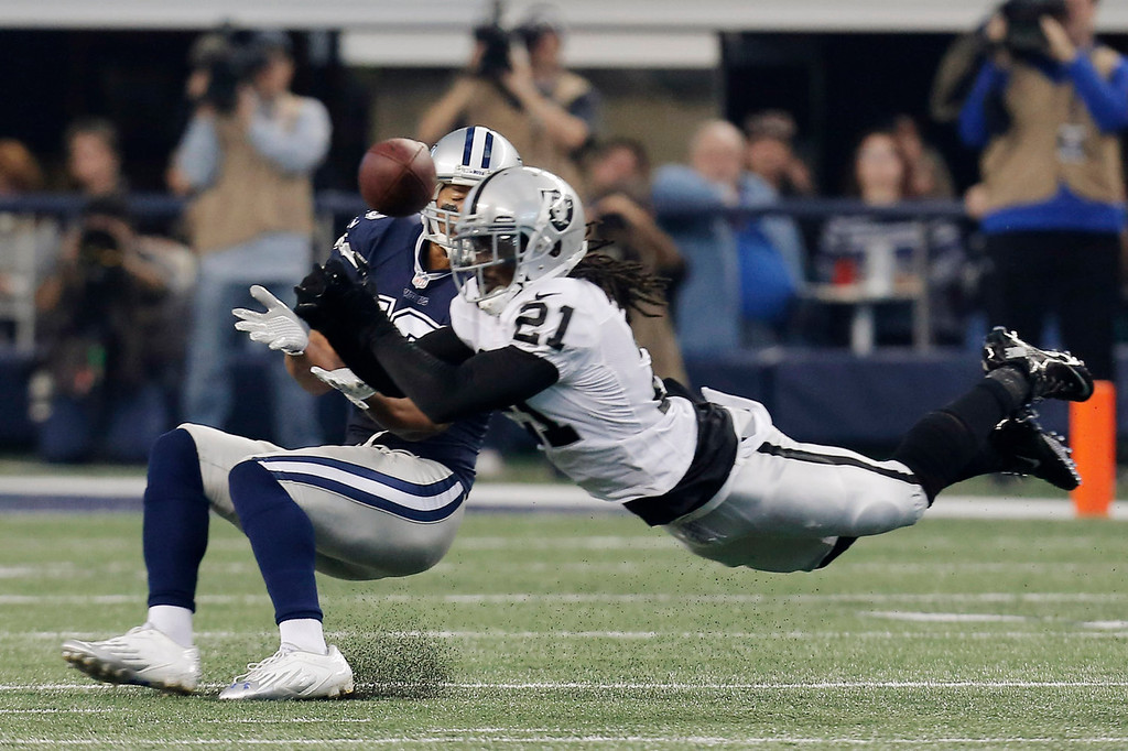 . Oakland Raiders cornerback Mike Jenkins (21) breaks up a pass to Dallas Cowboys wide receiver Miles Austin (19) during the first half of an NFL football game, Thursday, Nov. 28, 2013, in Arlington, Texas.  (AP Photo/Brandon Wade)