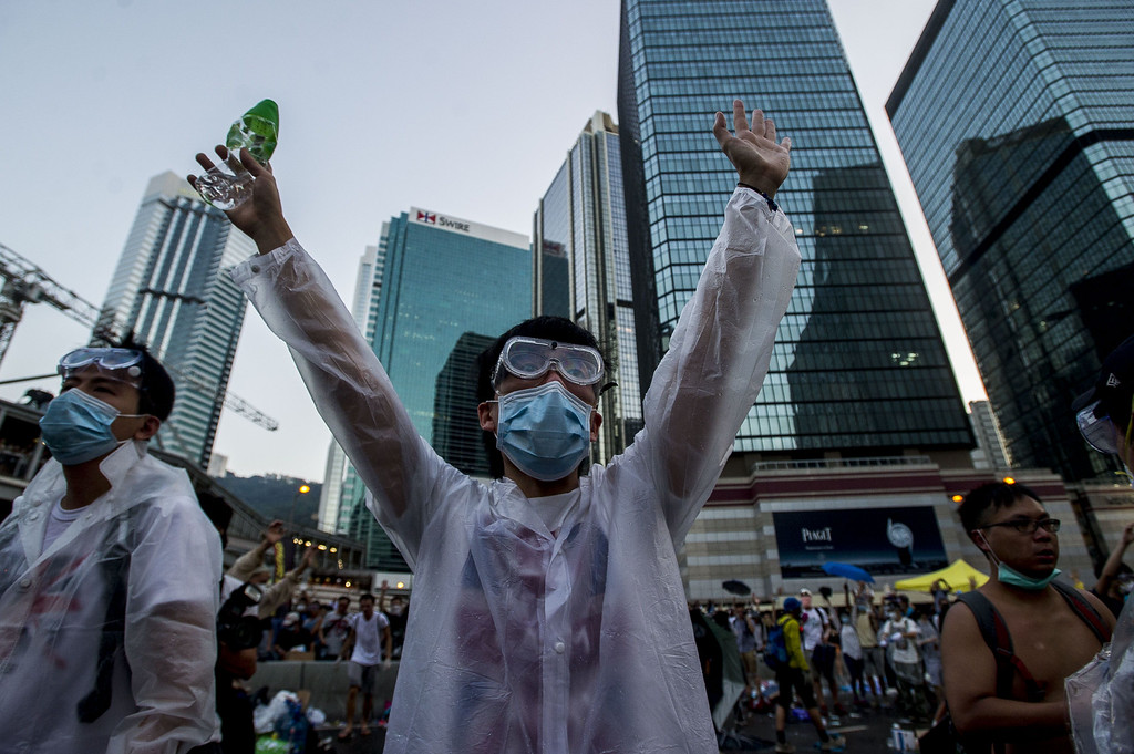 . A pro-democracy demonstrator wearing a mask and goggles to protect against pepper spray and tear gas gestures during a rally near the Hong Kong government headquarters on September 28, 2014. Police fired tear gas as tens of thousands of pro-democracy demonstrators brought parts of central Hong Kong to a standstill on September 28, in a dramatic escalation of protests that have gripped the semi-autonomous Chinese city for days. AFP PHOTO / XAUME OLLEROS