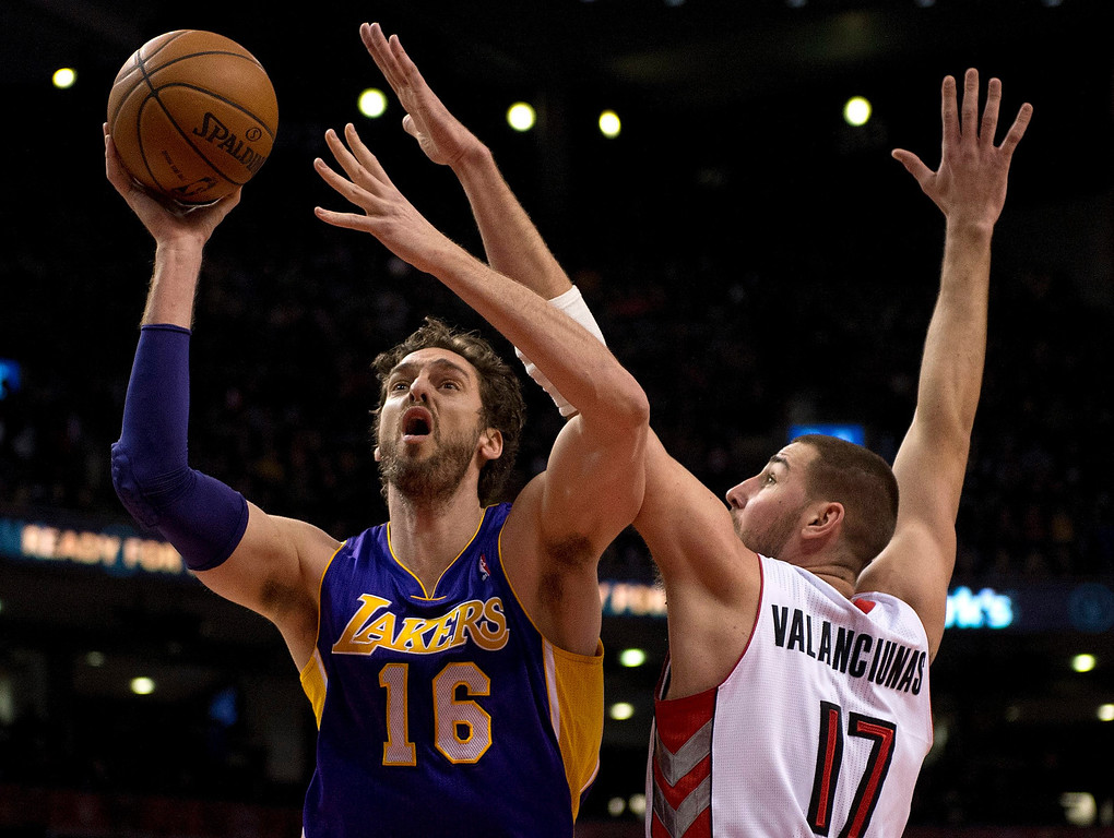 . Los Angeles Lakers center Pau Gasol (16) drives to the hoop past Toronto Raptors center Jonas Valanciunas during first-half NBA basketball game action in Toronto, Sunday, Jan. 19, 2014. (AP Photo/The Canadian Press, Frank Gunn)