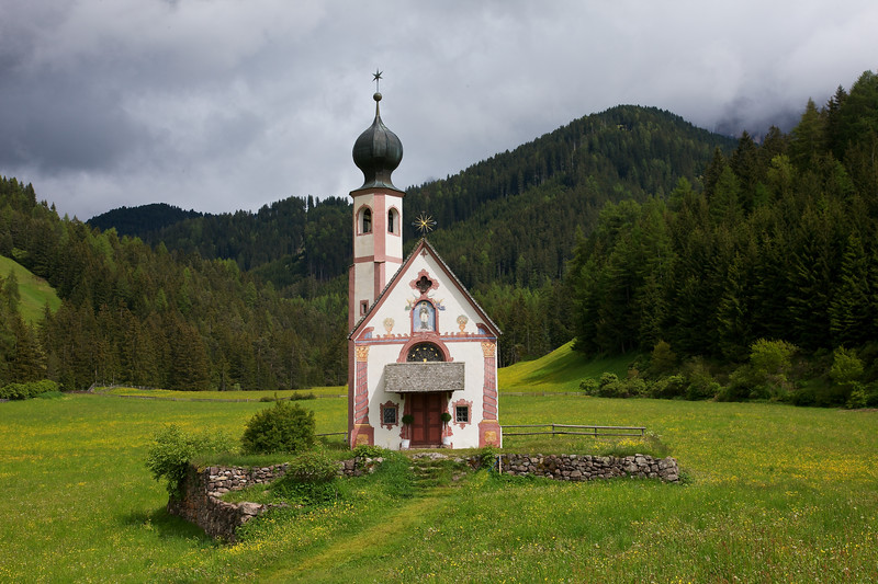 San Giovanni Church and Tower in the northern Italian valley of Val di Funes.  The small church is absolutely beautiful in the vast green valley.