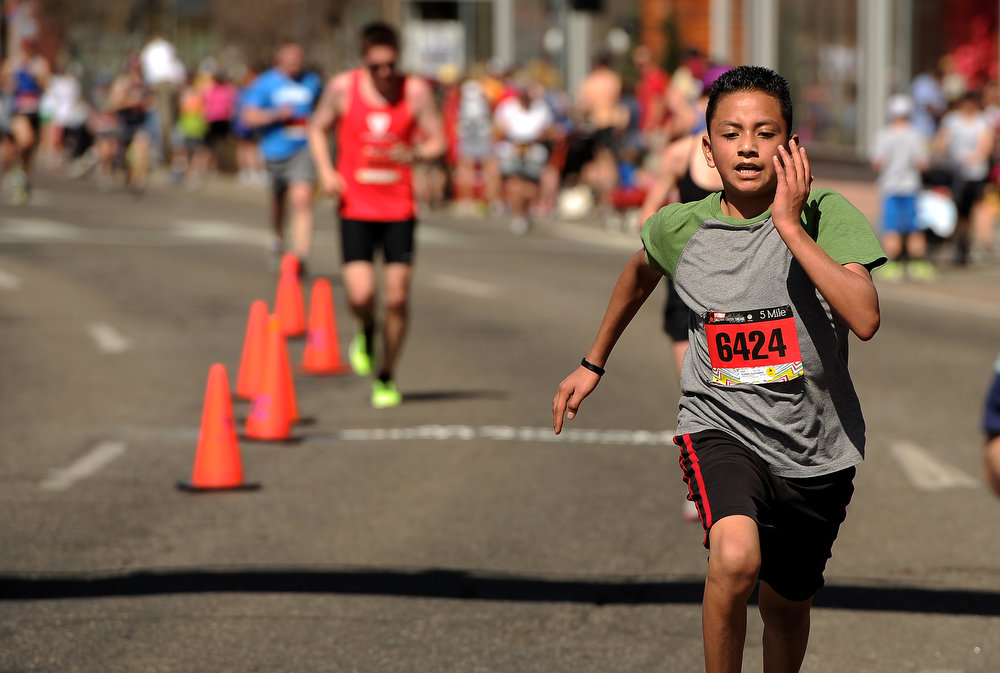 . Alex Aleman, 13, of Denver, gives it his all as he crosses the finish line after finishing the 5 mile race. : The 31st annual Cherry Creek Sneak had all sorts of distances for this year\'s race.  The Sneak, as it is affectionately named, had a 10 mile, 5 mile, 3.1 mile or 5K, a 1.5 mile Denver\'s 7 Sprint, and a kid\'s fun run for thousands of competitors, runners and walkers that turned out in the Cherry Creek neighborhood of Denver, CO on April 28, 2013.  The race is always held the last Sunday in April. This year participants cheered the national anthem and observed a moment of silence for victims of the Boston Marathon bombing at the start of each race. (Photo by Helen H. Richardson/The Denver Post)