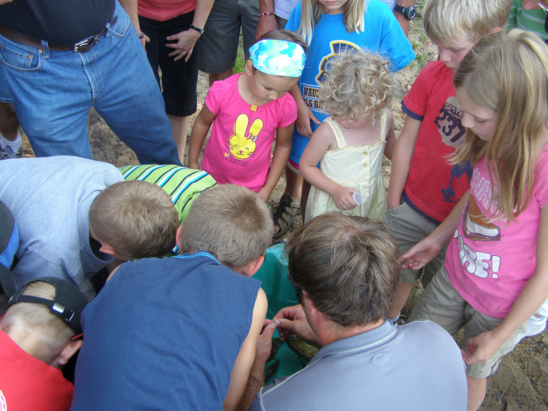 It doesn't take long for a swarm of kids to surround the tub, clamoring for a chance to hold a fish.