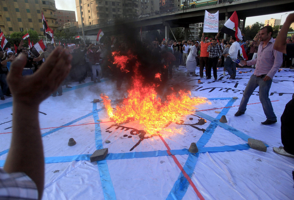 . Opponents of Egypt\'s Islamist President Mohammed Morsi burn an Israeli flag as they protest outside the ministry of defense in Cairo, Friday, June 28, 2013. Tens of thousands of backers and opponents of Egypt\'s Islamist president held competing rallies in the capital Friday and new clashes erupted between the two sides in the country\'s second largest city, Alexandria, in a prelude to massive nationwide protests planned by the opposition this weekend demanding Mohammed Morsi\'s removal. (AP Photo/Khalil Hamra)