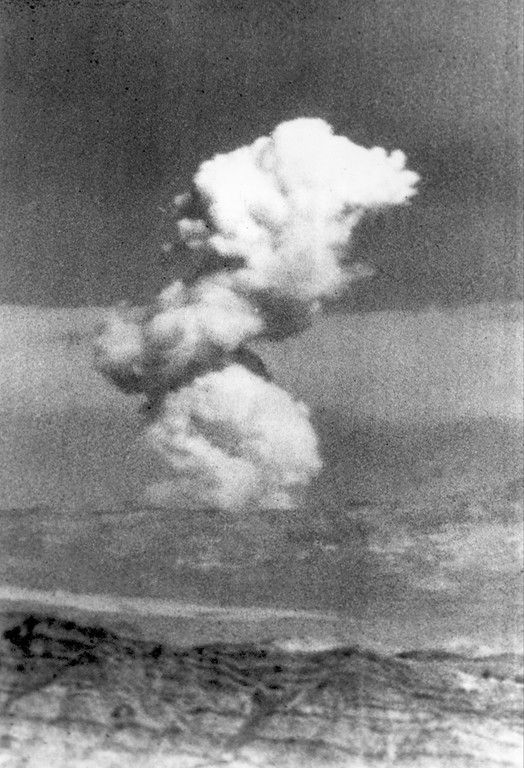 . A mushroom cloud rises over the Nevada Test Site (NTS) after the U.S. Atomic Energy Commission (AEC) detonated a low-yield nuclear weapons effects test in Mercury, Nev., 65 miles northwest of Las Vegas, July 11, 1962.  The device fired underground at a depth shallow enough to form a crater.  (AP Photo)