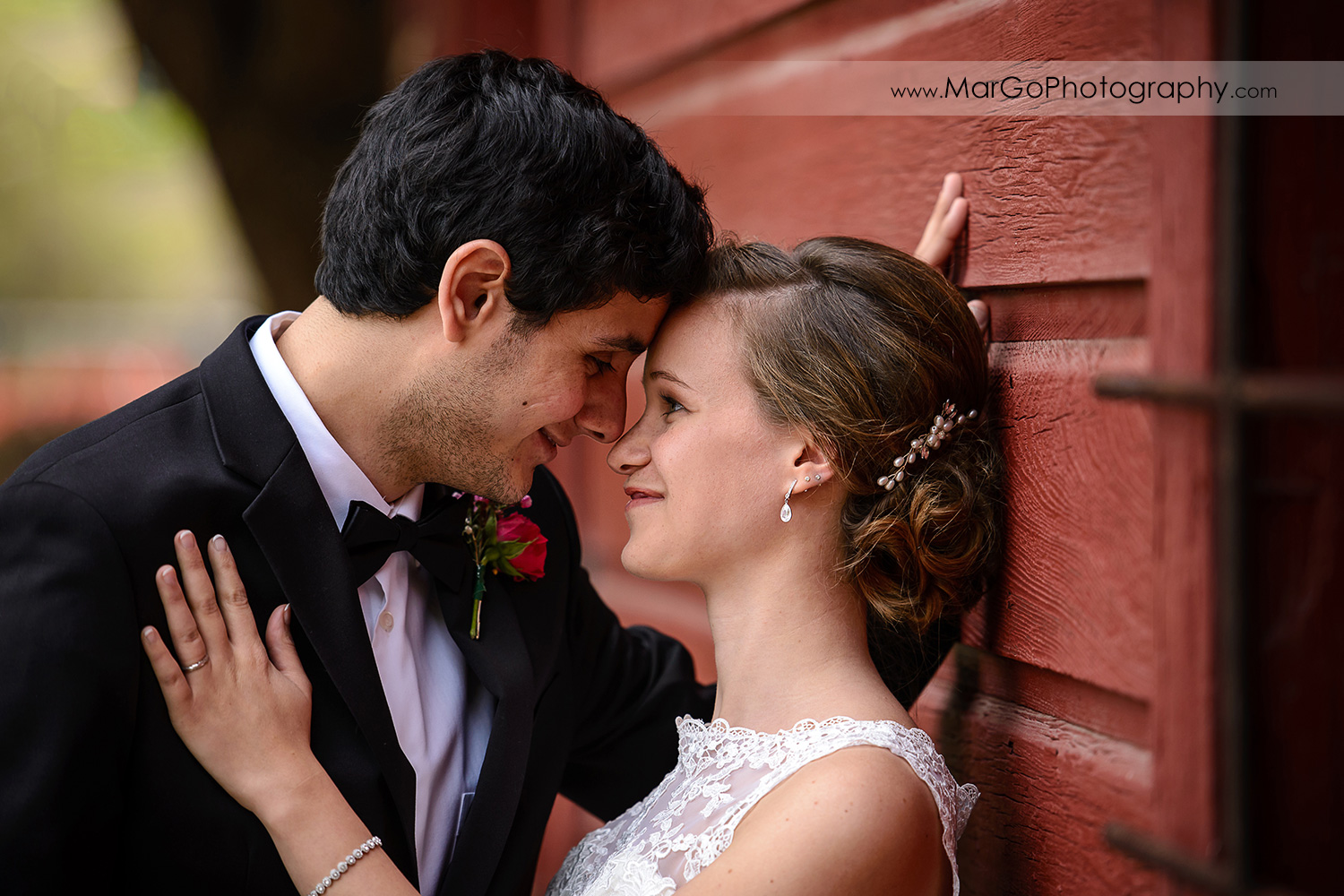 bride and groom snuggling noses at red barn wall during bridal session at Shinn Historical Park and Arboretum in Fremont