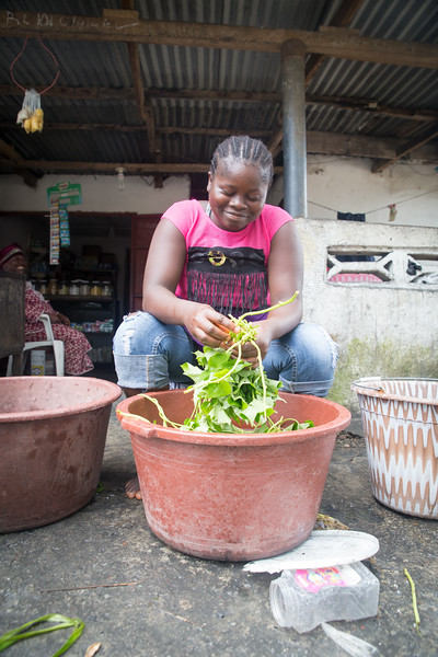 Monrovia, Liberia October 6, 2017 - A young girl cleans vegetables.
