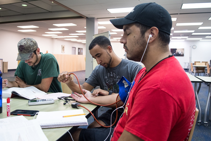 Christopher Were (center) collects vitals for his studies in the Mary and Jeff Bell Library.