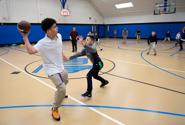 02/18/20 Wesley Bunnell | StaffrrKids play a game of indoor touch football in the gymnasium at the New Britain Boys and Girls Club on Tuesday afternoon. Janathan Villa, age 13, passes as he he is pressured by Jayvien Torres, age 9.