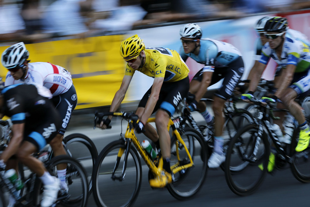 . Overall leader\'s yellow jersey Britain\'s Christopher Froome rides in the pack on the Champs Elysees avenue during the 133.5 km twenty-first and last stage of the 100th edition of the Tour de France cycling race on July 21, 2013 between Versailles and Paris.  JEFF PACHOUD/AFP/Getty Images