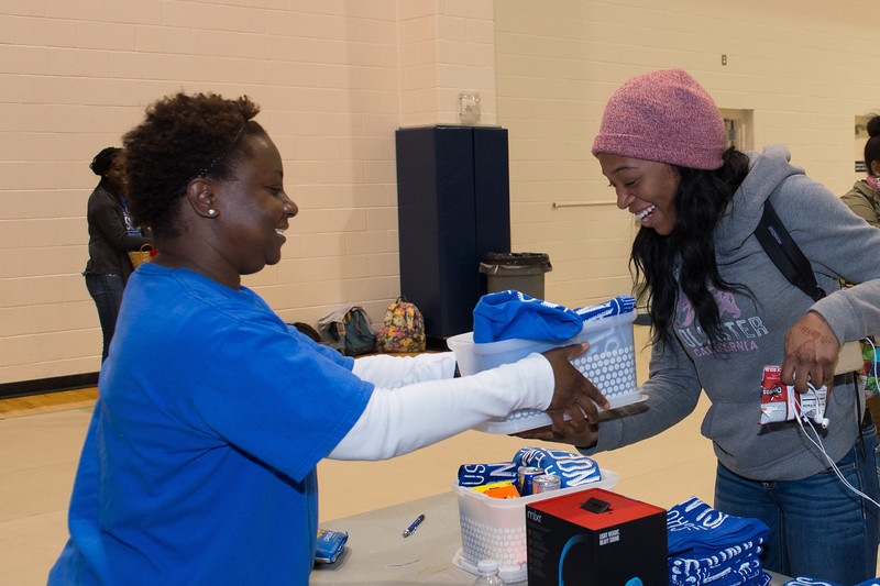 Priscilla Sanusi(right) receives her door prize at the homecoming Tip Off Picnic.
