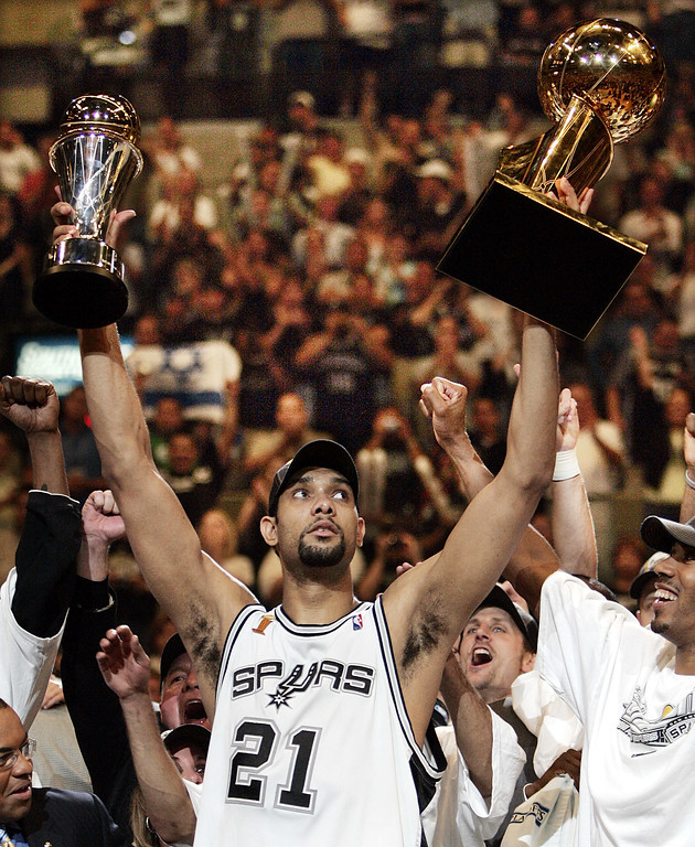 . FILE - In this June 23, 2005, file photo, San Antonio Spurs\' Tim Duncan (21) holds his MVP trophy, left, and the NBA basketball Championship trophy, right, after San Antonio won 81-74 to win the championship in Game 7 of the NBA finals in San Antonio. Duncan announced his retirement on Monday, July 11, 2016, after 19 seasons, five championships, two MVP awards and 15 All-Star appearances. It marks the end of an era for the Spurs and the NBA. (AP Photo/Eric Gay, File)