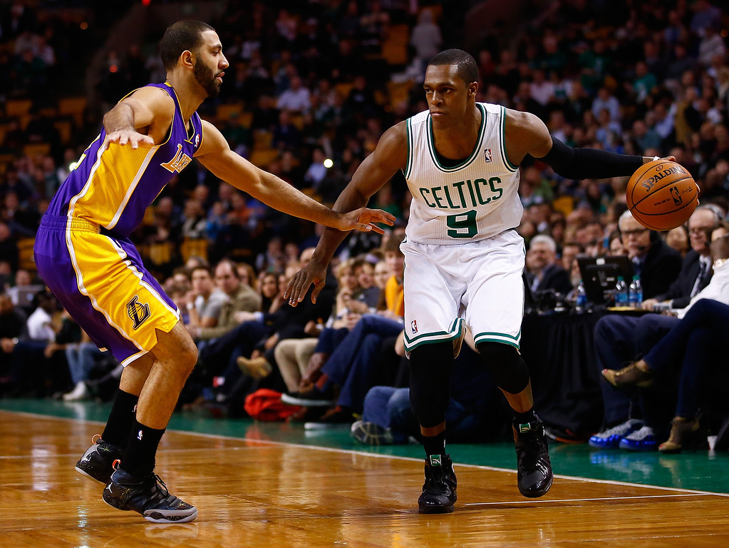 . BOSTON, MA - JANUARY 17:  Rajon Rondo #9 of the Boston Celtics handles the ball in front of Kendall Marshall #12 of the Los Angeles Lakers in the first quarter during the game at TD Garden on January 17, 2014 in Boston, Massachusetts.   (Photo by Jared Wickerham/Getty Images)