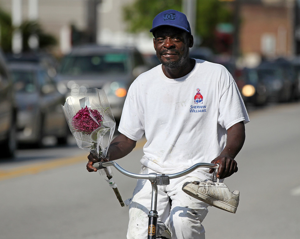 . Dexter Jenkins arrives on his bicycle to leave flowers at a memorial in front of the Emanuel AME Church on Friday, June 19, 2015 in Charleston, S.C.  Dylann Storm Roof, 21, is accused of killing nine people during a Wednesday night Bible study at the church.   ( Curtis Compton/Atlanta Journal-Constitution via AP)
