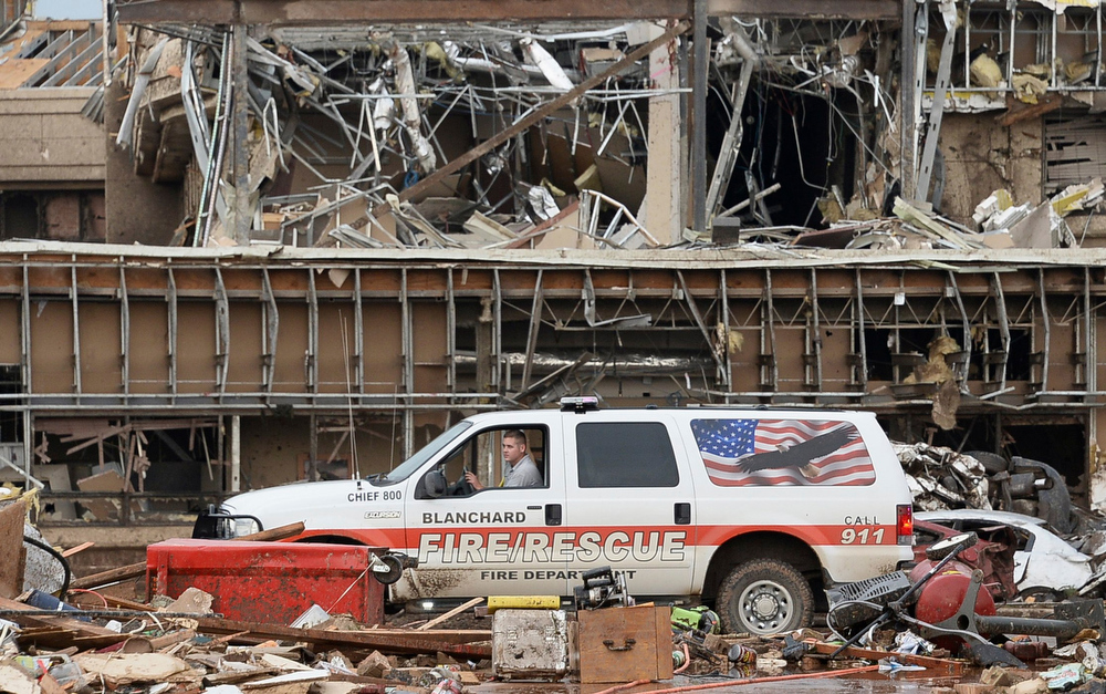 . A fire official drives through the rubble of Moore Medical Center after a tornado struck Moore, Oklahoma, May 20, 2013. A 2-mile-wide (3-km-wide) tornado tore through the Oklahoma City suburb of Moore on Monday, killing at least 51 people while destroying entire tracts of homes, piling cars atop one another, and trapping two dozen school children beneath rubble. REUTERS/Gene Blevins