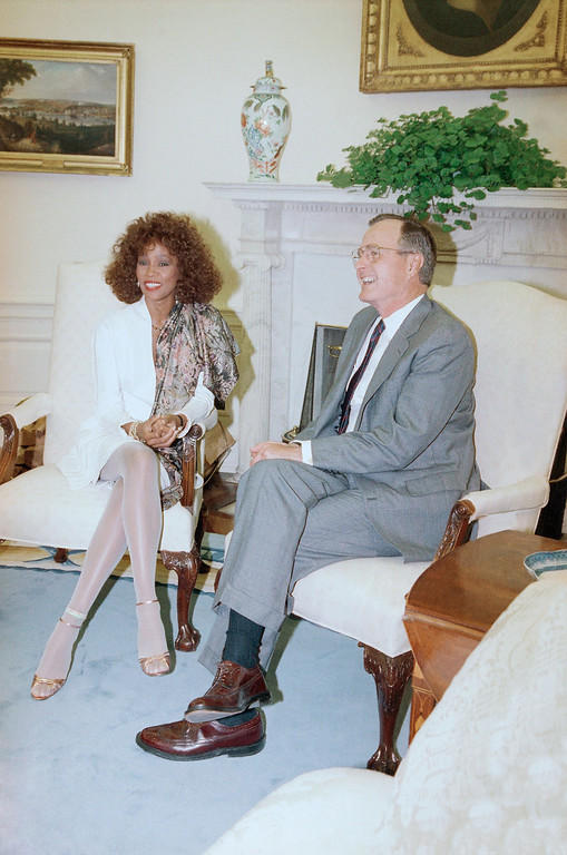 . U.S. President George H. Bush shares a laugh with performer Whitney Houston in the Oval Office of the White House, Wednesday, May 2, 1990 in Washington.  (AP Photo/Barry Thumma)
