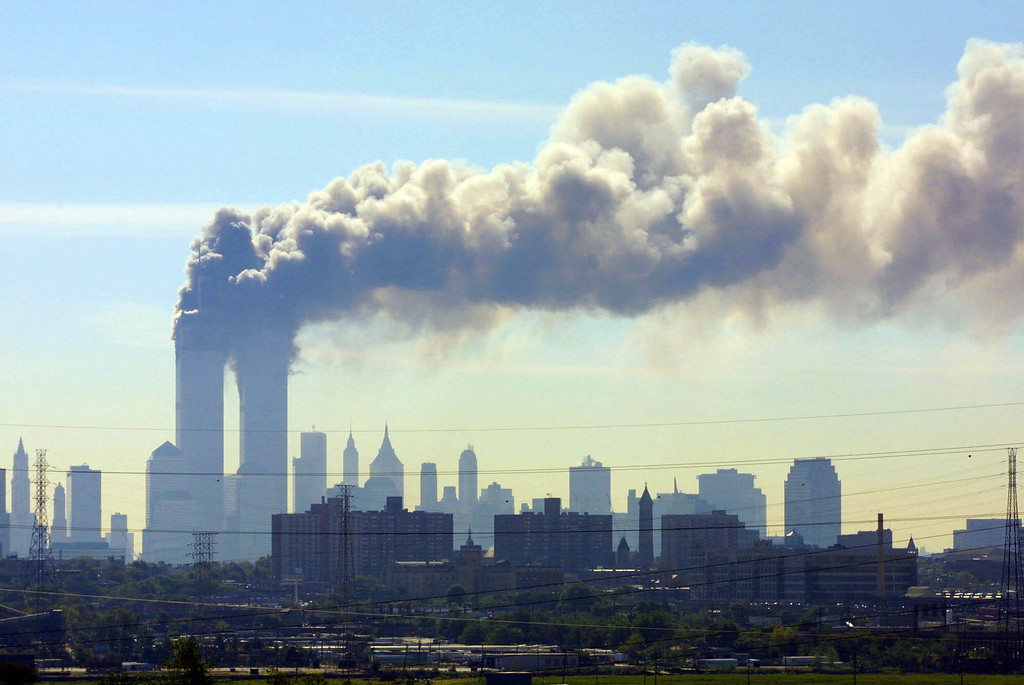 . As seen from the New Jersey Turnpike near Kearny, N.J., smoke billows from the twin towers of the World Trade Center in New York after airplanes crashed into both towers Tuesday, Sept.11, 2001. (AP Photo/Gene Boyars)