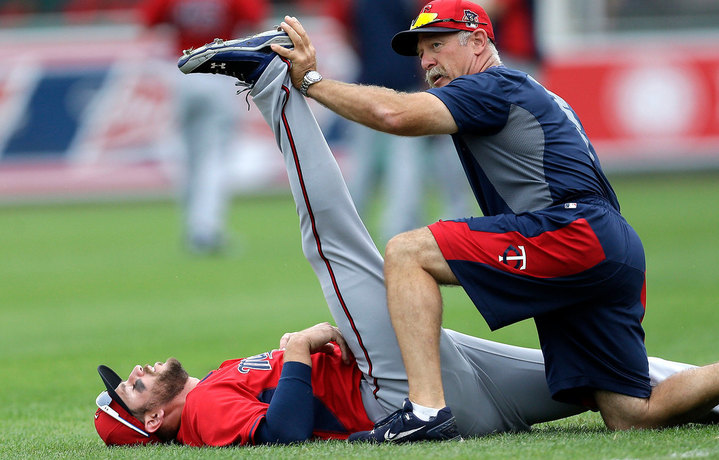 . Minnesota Twins third baseman Trevor Plouffe (24) stretches with the help of a trainer before an exhibition baseball game against the Boston Red Sox in Fort Myers, Fla., Saturday, March 29, 2014. (AP Photo/Gerald Herbert)