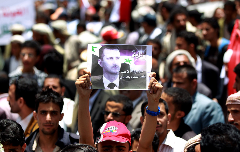 . Pro-Syrian regime activists, one holding up a poster of Syrian President Bashar al-Assad, shout slogans during a march against the Israeli attacks on Syria as they rally outside the United Nations offices in the capital Sanaa, on May 7, 2013. Israeli air raids on Syria at the weekend killed at least 42 soldiers, a watchdog said, fuelling international concern over a spillover of the conflict, as Damascus warned it would strike back.  MOHAMMED HUWAIS/AFP/Getty Images